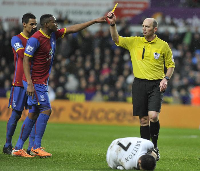 Referee Mike Dean, right, shows a yellow card to Crystal Palace's Mile Jedinak, not pictured, during the English Premier League soccer match between Swansea City and Crystal Palace at the Liberty Stadium, Swansea, Wales, Sunday, March 2, 2014. (AP Photo/PA) UNITED KINGDOM OUT - NO SALES - NO ARCHIVES
