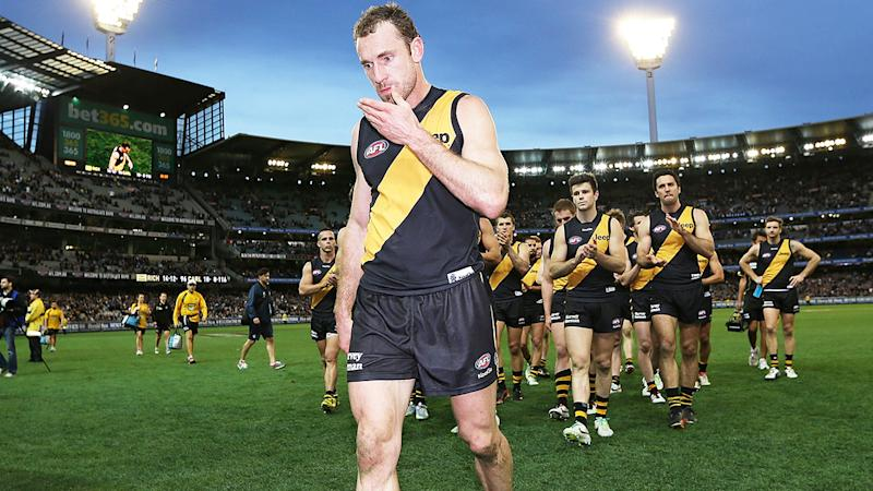 Shane Tuck is pictured being clapped off the field by his teammates in 2013.