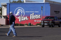 A pedestrian crosses the street in Van Horn, Texas, Monday, Oct. 11, 2021. Tuesday's Blue Origin launch near the city has been pushed to Wednesday due to weather. (AP Photo/LM Otero)