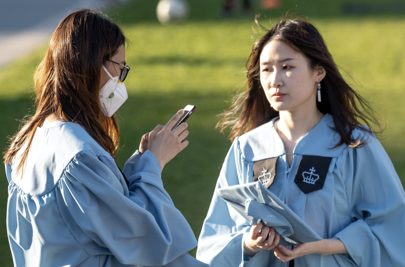 A Columbia University student wearing a mask takes photos with her fellow students in their cap and gowns amid the coronavirus pandemic on April 28, 2020 in New York City, New York. (Photo: Alexi Rosenfeld/Getty Images)