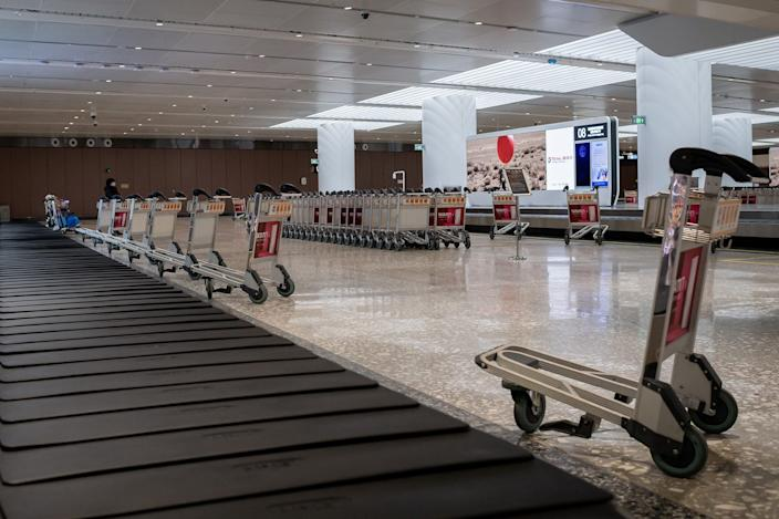 This picture taken on February 14, 2020 shows an arriving passenger (back L) wearing a face mask while standing in an empty baggage claim area at Daxing 2