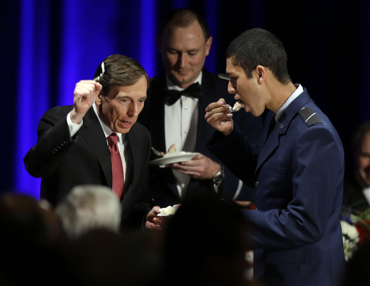 David H. Petraeus, former army general and head of the Central Intelligence Agency, tastes a ceremonial cake presented to him by Hector Sandoval, a member of the USC ROTC program, at the annual dinner for veterans and ROTC students at the Univeristy of Southern California, in downtown Los Angeles Tuesday, March 26, 2013. It marked Petraeus' first public remarks since he retired as head of the CIA after an extramarital affair scandal. (AP Photo/Reed Saxon)