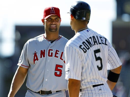 Los Angeles Angels first baseman Albert Pujols, left, jokes with Colorado Rockies baserunner Carlos Gonzalez who takes first base after hitting a single in the ninth inning of the Angels' 11-5 victory in a baseball game in Denver, Saturday, June 9, 2012. (AP Photo/David Zalubowski)