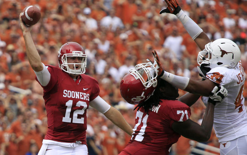 Oklahoma quarterback Landry Jones (12) passes as offensive linesman Tyrus Thompson (71) blocks Texas defensive end Jackson Jeffcoat (44) during the first half of an NCAA college football game at the Cotton Bowl Saturday, Oct. 13, 2012, in Dallas. (AP Photo/LM Otero)