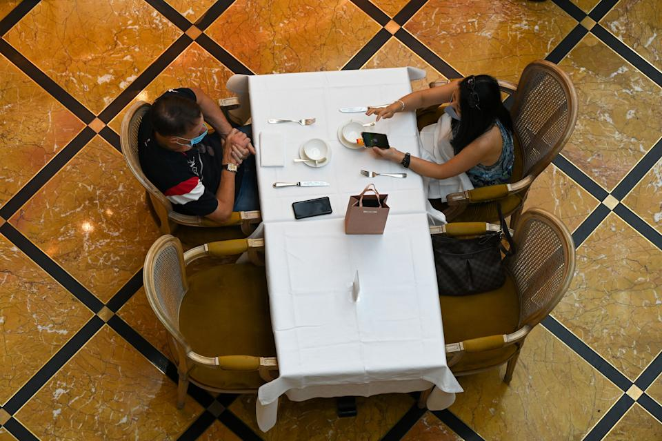 People dine at a restaurant in a shopping mall on 14 May. (PHOTO: Getty Images)