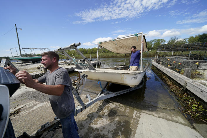 Charles Russ and Allan Bergeron, right, pull their boat from the water after pulling their crab traps from Bayou Dularge in anticipation of Hurricane Delta, expected to arrive along the Gulf Coast later this week, in Theriot, La., Wednesday, Oct. 7, 2020. (AP Photo/Gerald Herbert)