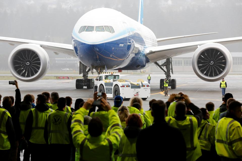 Boeing employees and others watch a Boeing 777X airplane return to a hangar after its first test flight: REUTERS