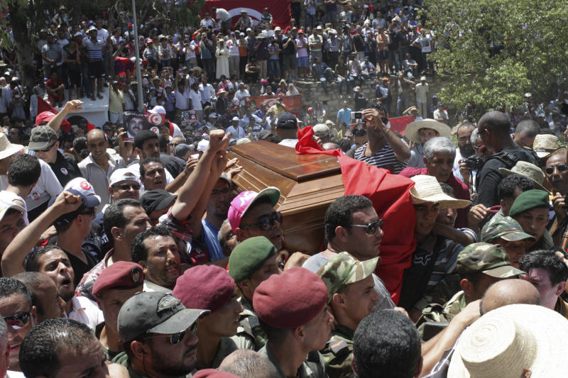 Tunisians carry the coffin of Tunisian opposition politician Mohammed Brahmi during his funeral at Jallez Cemetery in Tunis, Saturday July, 27, 2013. Mohamed Brahmi was shot 14 times in front of his home within sight of his family on Thursday, plunging the country into a political crisis and unleashing demonstrations around the country blaming the government for the assassination. (AP Photo/Amine Landoulsi)