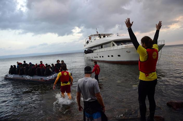 A man gestures from shore as migrants and refugees arrive on a rubber dinghy on the Greek island of Lesbos after crossing the Aegean Sea from Turkey on November 21, 2015 (AFP Photo/Bulent Kilic)