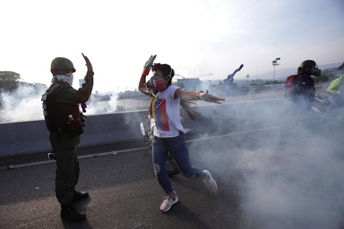 An opponent to Venezuela's President Nicolas Maduro high fives a rebel soldier on a highway overpass outside La Carlota air base amid tear gas fired by loyalist soldiers inside the base in Caracas, Venezuela, Tuesday, April 30, 2019. Venezuelan opposition leader Juan Guaida took to the streets in Caracas with activist Leopoldo Lopez and a small contingent of heavily armed troops early Tuesday in a bold and risky call for the military to rise up and oust socialist leader Nicolas Maduro. (Photo: Boris Vergara/AP)