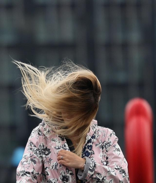 The wind catches a woman's hair in London as Storm Francis hit the UK on August 25