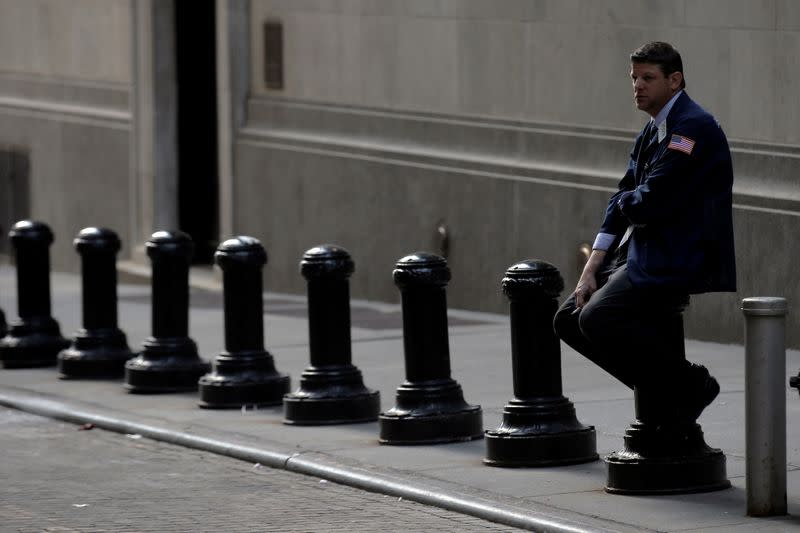 A trader takes a break outside the NYSE on Wall Street in New York