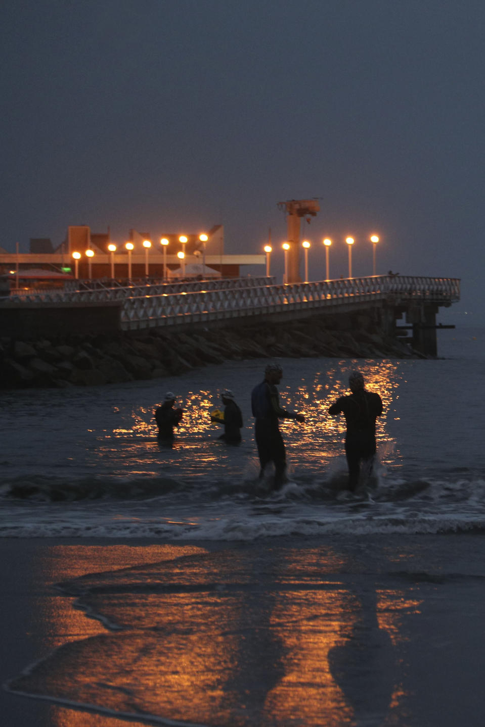 Swimmers arrive near a pier at Pescadores beach in Lima, Peru at sunrise, Tuesday, April 27, 2021. One of the few sporting disciplines that have been maintained during the coronavirus pandemic is swimming, which due to the closure of the swimming pools, has moved to the open sea. (AP Photo/Martin Mejia)