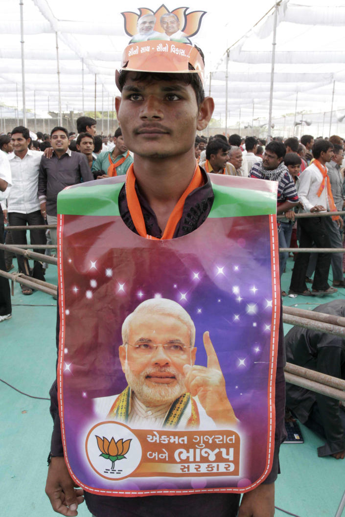 In this Monday, Dec. 3, 2012 photo, a supporter sports a poster of Gujarat Chief Minister Narendra Modi during an election campaign at Viramgam, Gujarat, India. Eleven years after Modi became the chief minister of the western state of Gujarat - and 10 years after brutal anti-Muslim rioting left over a 1,100 people there dead - Modi is campaigning for his third term. Nearly everyone expects him to be swept into office, and the top leadership of his rightwing Bharatiya Janata Party is already hailing him as a future prime minister. But few politicians in India are as polarizing as Modi. (AP Photo/Ajit Solanki)