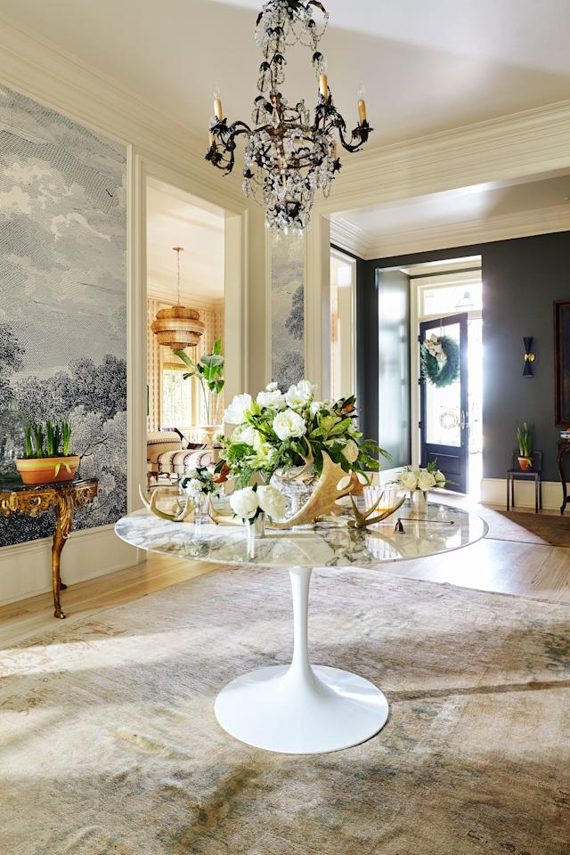 """<p>A green-and-white floral arrangement in the foyer is every bit as sophisticated as the neutral background of creams, whites, blushes, and blacks that frames it. The bouquet is set in a silver punch bowl that Colhoun inherited, a piece that Ludwig found to be just the right size and shape for the table. Don't fear widemouthed vessels: They are as easy to use as skinny ones and offer the opportunity to create more dynamic arrangements that """"drape and flow,"""" says Ludwig. A mix of naturally shed and resin-cast (artificial) antlers adds earthiness while also picking up the room's creamy tones.</p>"""