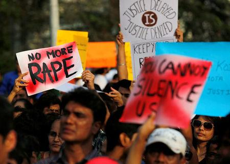 People hold placards as they participate in a protest against the rape of an eight-year-old girl in Kathua near Jammu, and a teenager in Unnao, Uttar Pradesh state, in Mumbai, India, April 15, 2018. REUTERS/Danish Siddiqui