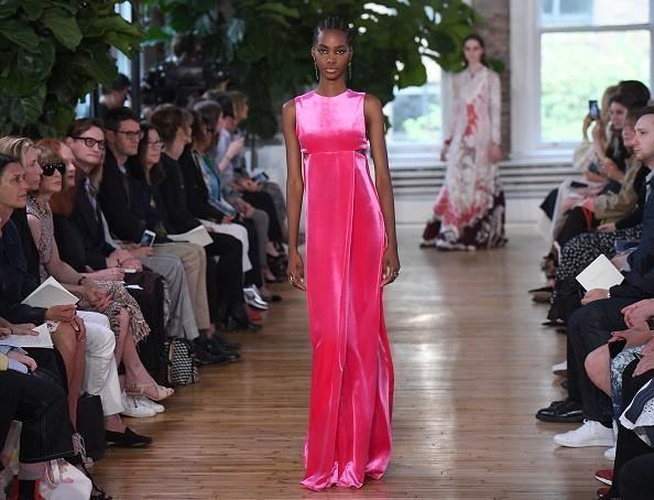 <p>A model walks the runway in a hot pink dress for the Valentino Resort 2018 runway show in New York City. (Photo: Getty Images) </p>