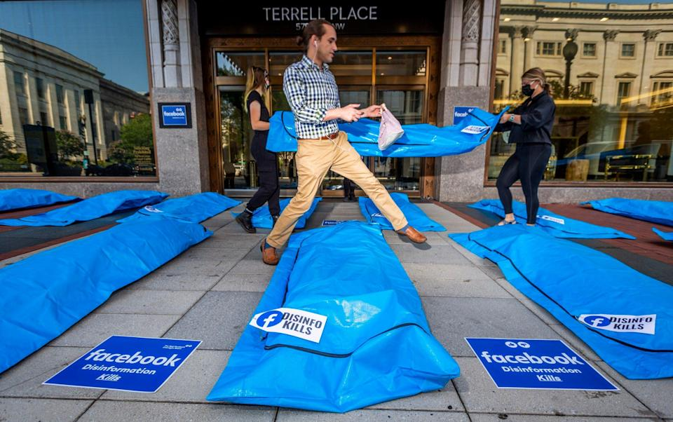"""A passing pedestrian holding a plastic bag and with white ear buds in his ears steps gingerly over plastic body bags laid out on the pavement outside a mirrored-glass building facade. Each bag has a tag bearing the Facebook logo and the message """"disinfo kills"""", and appears to be stuffed with material so that it looks occupied. In the background, two people in black clothes and face masks carry another bag past the camera. - Eric Kayne/AP"""