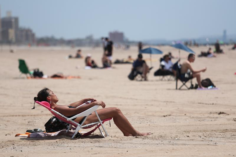 A woman sunbathes during warm weather at Coney Island in the Brooklyn borough of New York, U.S., May 20, 2019. REUTERS/Shannon Stapleton