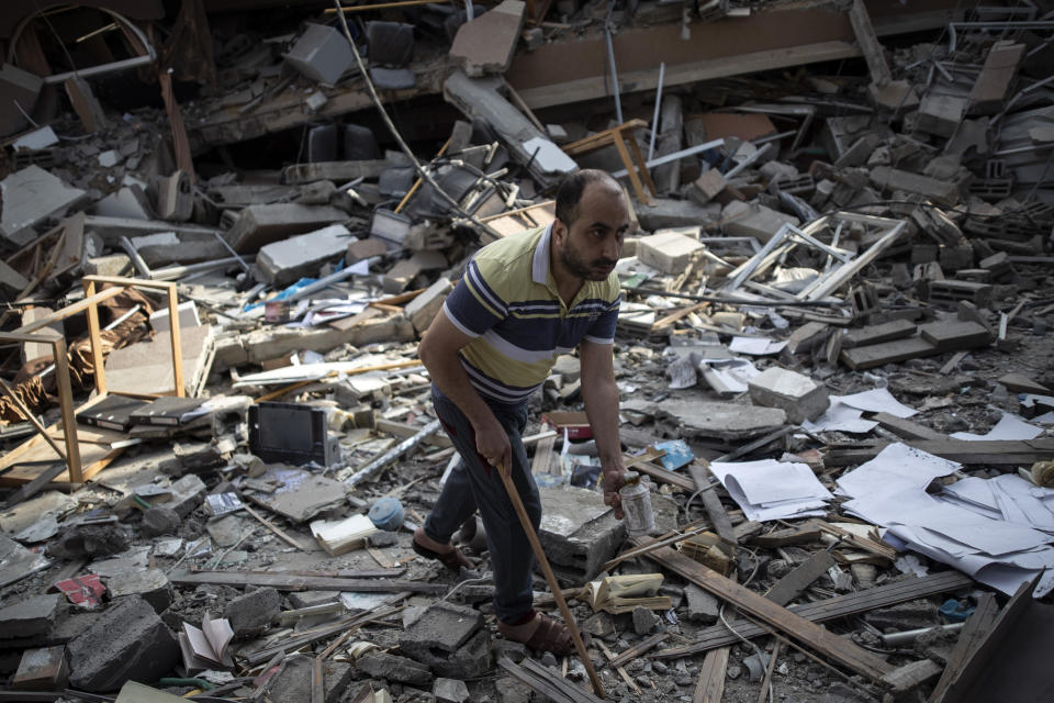A Palestinian man inspects the damage of a house destroyed by an early morning Israeli airstrike, in Gaza City, Tuesday, May 18, 2021. Israel carried out a wave of airstrikes on what it said were militant targets in Gaza, leveling a six-story building in downtown Gaza City, and Palestinian militants fired dozens of rockets into Israel early Tuesday, the latest in the fourth war between the two sides, now in its second week. (AP Photo/Khalil Hamra)