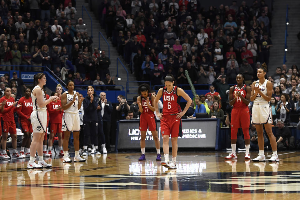 Connecticut players and US National players stand for a 24 second shot-clock violation to honor Kobe Bryant during an exhibition basketball game in the first half of a basketball game, Monday, Jan. 27, 2020, in Hartford, Conn. (AP Photo/Jessica Hill)