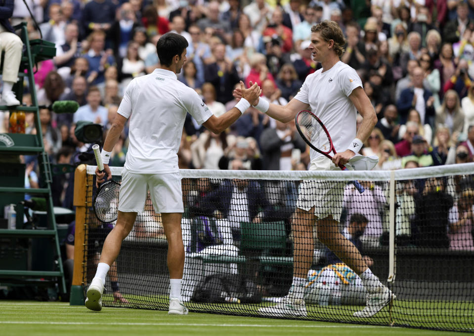 Serbia's Novak Djokovic shakes hands with South Africa's Kevin Anderson, right, after winning the men's singles second round match on day three of the Wimbledon Tennis Championships in London, Wednesday June 30, 2021. (AP Photo/Alastair Grant)