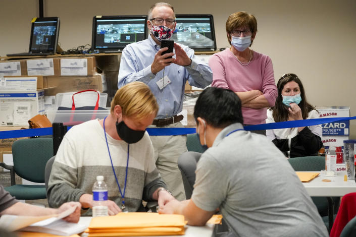 Republican canvas observer Ed White, center, and Democratic canvas observer Janne Kelhart, watch as Lehigh County workers count ballots as vote counting in the general election continues, Friday, Nov. 6, 2020, in Allentown, Pa. (AP Photo/Mary Altaffer)