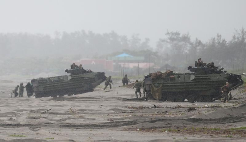 Philippine and US marines take their position next to Amphibious Assault vehiclle (AAV) during a beach landing as part of the Philippines-US amphibious landing exercise (PHIBLEX) at a naval training base facing South China sea (AFP Photo/Ted Aljibe)