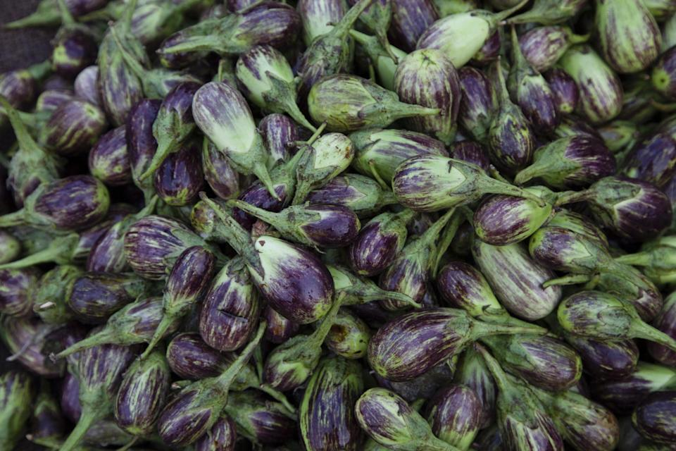 A large number of Thai purple eggplants are violet and streaked with white
