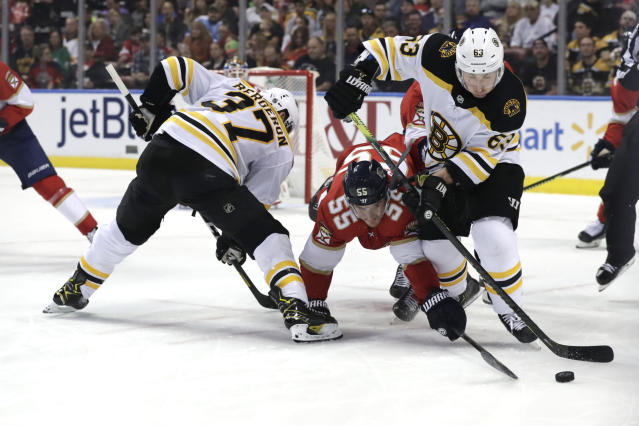 Florida Panthers center Noel Acciari (55) and Boston Bruins left wing Brad Marchand (63) fight for the puck during the first period of an NHL hockey game, Saturday, Dec. 14, 2019, in Sunrise, Fla. (AP Photo/Lynne Sladky)