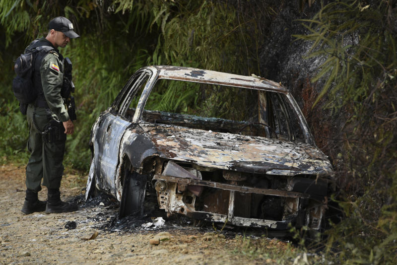 A police officer looks at a vehicle incinerated during a skirmish between illegal armed groups in which at least five people were killed in Jamundi, southwest Colombia, Friday, Jan. 17, 2020. Authorities say rebels with the former Revolutionary Armed Forces of Colombia operate in the area and may have been involved. (AP Photo/Christian EscobarMora)