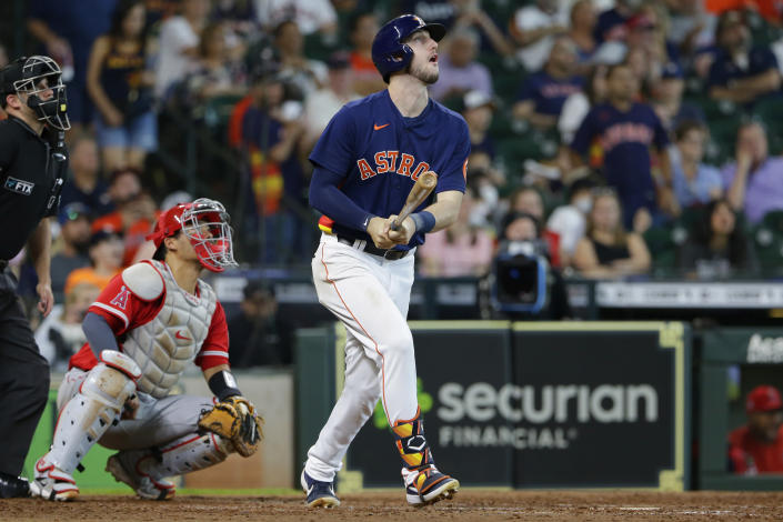 Houston Astros' Kyle Tucker, right, watches his two-run home run in front of Los Angeles Angels catcher Kurt Suzuki, second from left, during the sixth inning of a baseball game Sunday, Sept. 12, 2021, in Houston. (AP Photo/Michael Wyke)