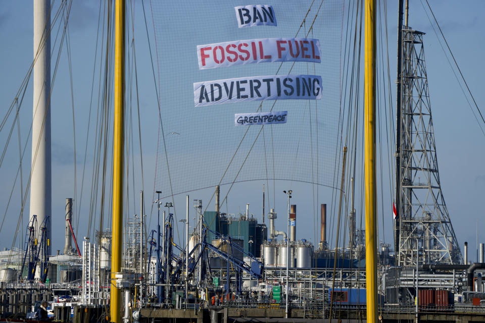 """Greenpeace's Beluga II carries a banner reading """"Ban Fossil Fuel Advertising"""" as it blocks part of the port at a Shell refinery in Rotterdam, Netherlands, Monday, Oct. 4, 2021. A coalition of environmental groups launched a campaign calling for a Europe-wide ban on fossil fuel advertising ahead of the United Nations Climate Change Conference, also known as COP26, which start in Glasgow on Oct. 31st, 2021. (AP Photo/Peter Dejong)"""