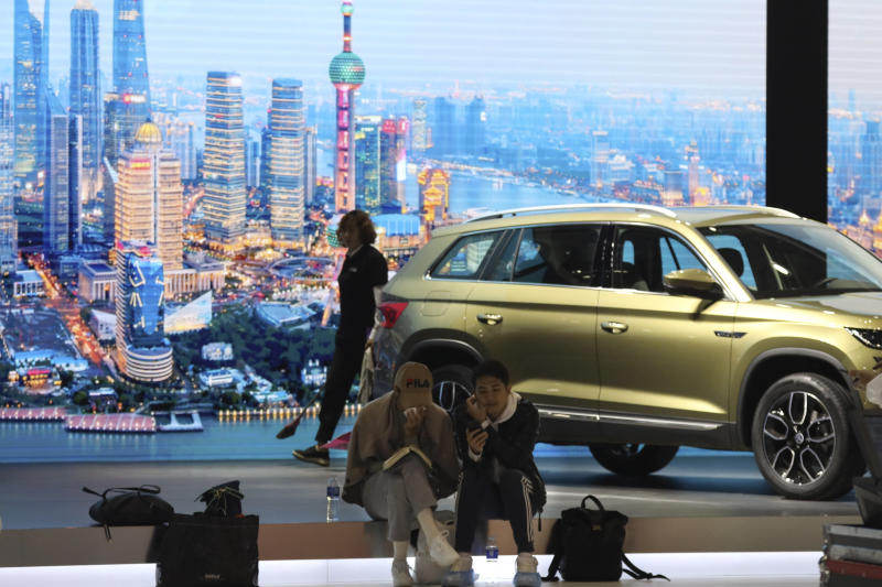 In this April 15, 2019, photo, visitors rest near a booth at the Auto Shanghai 2019 show in Shanghai. China's auto sales sank 5.4% in November from a year ago, putting the industry's biggest global market on track to shrink for a second year, an industry group reported Tuesday, Dec. 10, 2019. (AP Photo/Ng Han Guan)