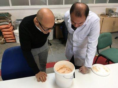 Lancaster University researchers Professor Mohamed Saafi and Hasan Hasan look into a bucket containing carrot mixture to be added to concrete, in their laboratory in Lancaster, Britain October 2, 2018. REUTERS/Jim Drury