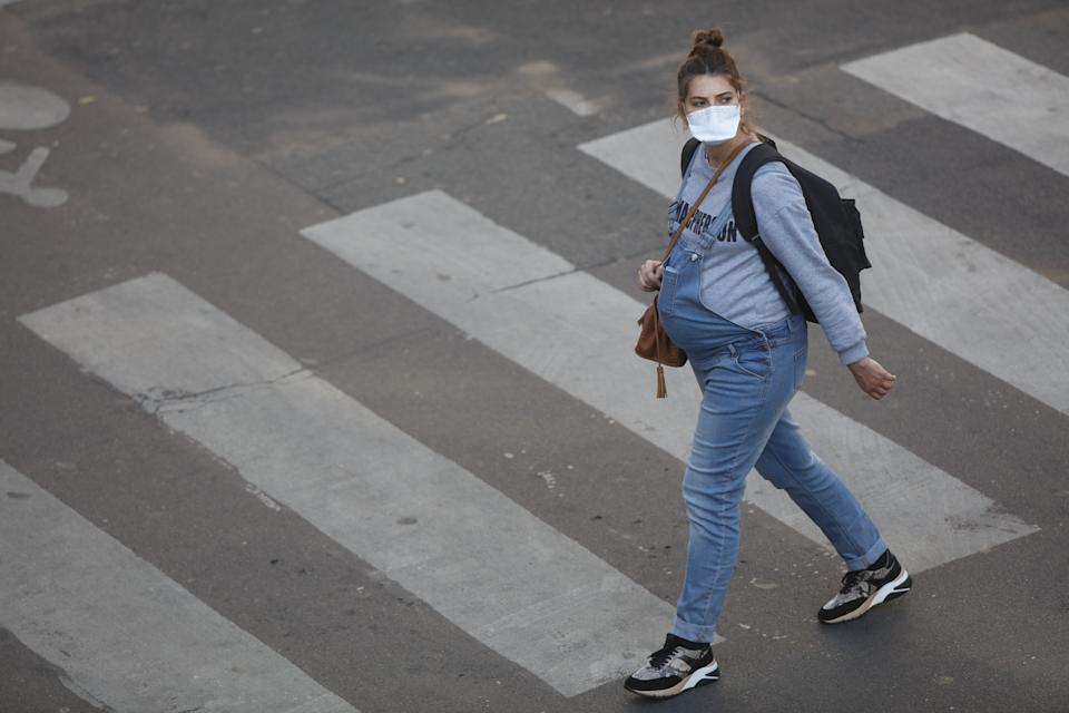 A pregnant women with a protective mask walks on the street in Paris, on April 8, 2020, during the lockdown in France to attempt to halt the spread of the novel coronavirus COVID-19.   (Photo by Mehdi Taamallah/NurPhoto via Getty Images)
