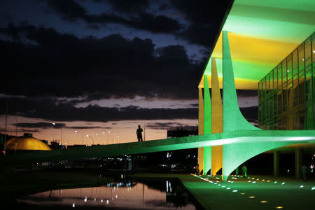A security guard walks in front of the Planalto Palace as it is lit up in the colours of the Brazilian national flag ahead of the 2014 World Cup in Brasilia