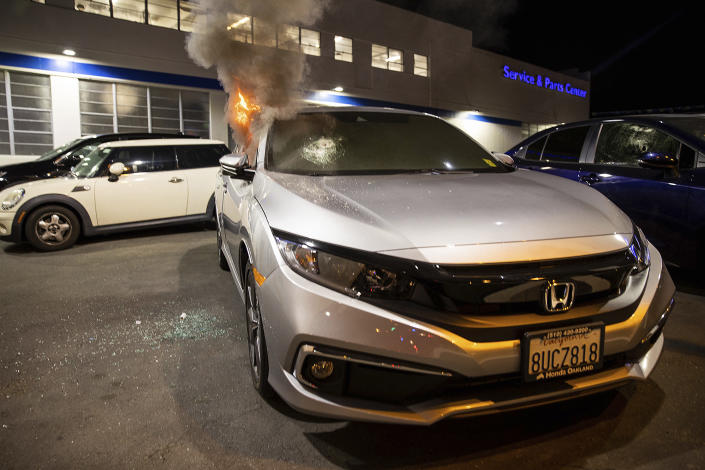 A car is set on fire at a Honda car dealership during a protest against police brutality in Oakland, Calif., on Friday, April 16, 2021. (AP Photo/Ethan Swope)