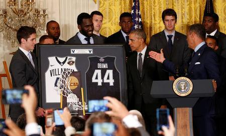 FILE PHOTO: U.S. President Barack Obama receives a gift as he honors Villanova University's men's 2016 NCAA championship basketball team at the White House in Washington May 31, 2016. REUTERS/Kevin Lamarque/File Photo
