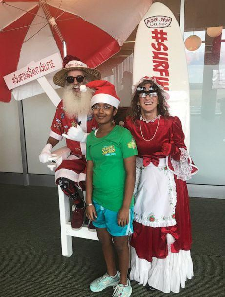 PHOTO: Charlotte Cornell, 14, poses for a photo with Mr. and Mrs. Claus from the Surfing Santa group from Florida's Space Coast during a visit to AdventHealth for Children's Hospital in Orlando, Fla. (Courtesy George Trosset/Surfing Santas)