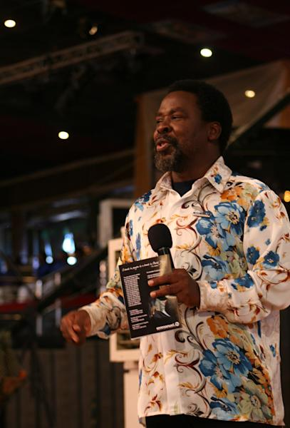 """FILE - In this Sunday, Sept. 15, 2013 file photo, T.B. Joshua conducts a service at the Synagogue, Church of All Nations, in Lagos Nigeria. T.B. Joshua's Synagogue, Church of All Nations has branches around the world, and a recent YouTube video even credits him with predicting the disappearance of Malaysian Airlines Flight MH370. Joshua is one of the best-known preachers in Africa and among the most profitable in Nigeria, the go-to faith healer and spiritual guide for leaders such as the late Ghanaian president John Atta Mills, Malawian president Joyce Banda and former Zimbabwean prime minister Morgan Tsvangirai. The man who says he comes from the poor village of Arigidi is worth between $10 and $15 million based on assets, according to Forbes magazine, which in 2011 estimated his personal wealth. The church holds some 15,000 people with outside tents for the overflow and Sunday services are beamed worldwide. Yet critics say this wildly popular televangelist hinders efforts to curtail the spread of HIV and tuberculosis with testimonies by church-goers that faith and his holy water can cure both. He is also accused of taking advantage of his followers and tightly controlling those closest to him, who call him """"Daddy.""""(AP Photo/Carley Petesch, file)"""