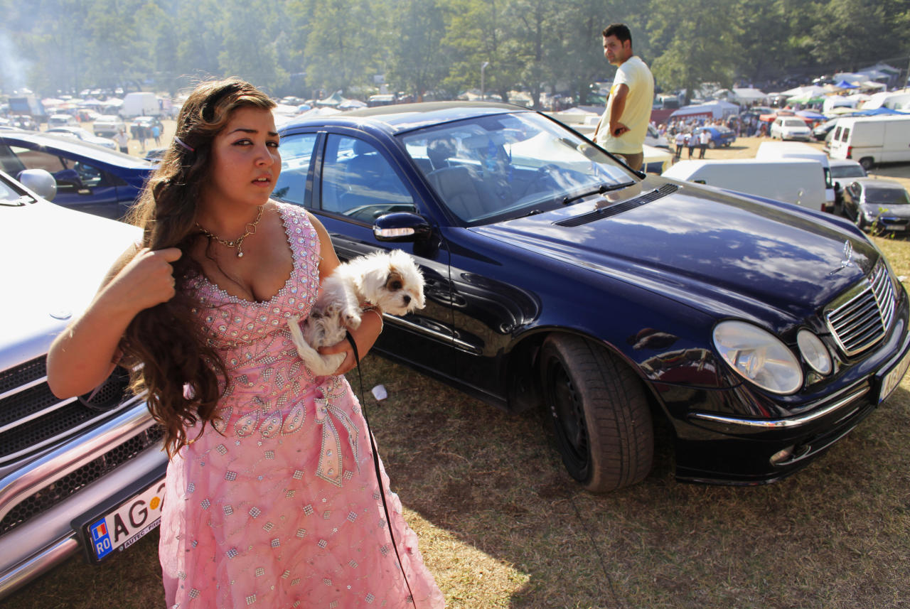 A Roma girl holds her pet dog during the traditional ethnic Roma festival in Costesti, 210 km (128 miles) west of Bucharest, September 8, 2012. Following their tradition, thousands of Roma from all over Romania, which has Europe's largest Roma community, gather every year to celebrate the birthday of St. Mary, to make wedding arrangements for their sons and daughters and to show off their wealth.   REUTERS/Radu Sigheti (ROMANIA - Tags: SOCIETY RELIGION ANIMALS)