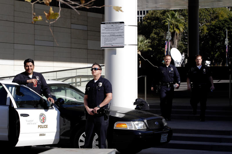 Los Angeles police officers stand alert at the LAPD headquarters in Los Angeles on Tuesday, Feb. 12, 2013. Police are now investigating more than 1,000 tips from the public in the search for the Christopher Dorner, who is suspected of a deadly revenge plot against the Los Angeles Police Department. The number of tips has grown from an initial 250 since the city offered a $1 million reward for information leading to the capture of Dorner. (AP Photo/Nick Ut)