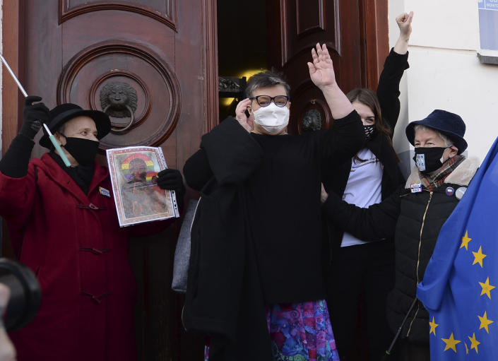 Polish activists Elzbieta Podlesna, center left, and Anna Prus, center right, surround by supporters as they leave court after being acquitted of desecration by a court in Plock, Poland, Tuesday March 2, 2021. A Polish court has acquitted three activists who had been accused of desecration for adding the LGBT rainbow to images of a revered Roman Catholic icon. In posters that they put up in protest in their city of Plock, the activists used the rainbow in place of halos on a revered image of the Virgin Mary and baby Jesus. (AP Photo/Czarek Sokolowski)