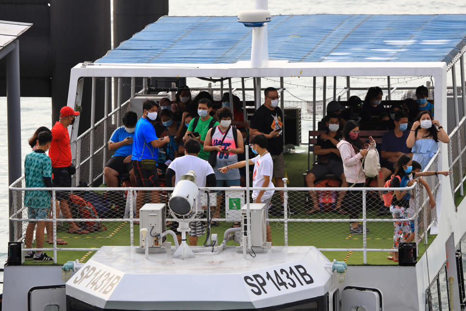 Passengers on board a ferry departing to a nearby offshore island at the Marina Bay Cruise Centre in Singapore.