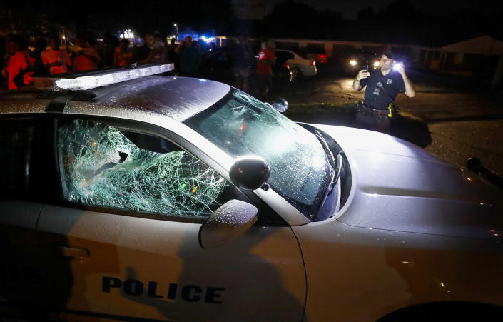A Memphis police officer looks over a damaged squad car after protesters took to the streets of the Frayser community in anger against the shooting a youth by U.S. Marshals earlier in the evening, Wednesday, June 12, 2019, in Memphis, Tenn. Dozens of protesters clashed with law enforcement, throwing stones and tree limbs until authorities broke up the angry crowd with tear gas. (Photo: Mark Weber/Daily Memphian via AP)