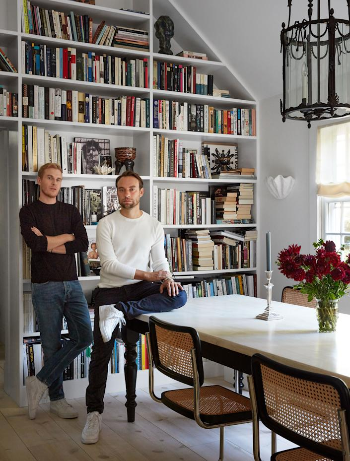 """<div class=""""caption""""> McGrath (left) and Leandro in the dining room, which they lined with built-in bookshelves and furnished with Marcel Breuer chairs place around a farm table. </div> <cite class=""""credit"""">Stephen Kent Johnson</cite>"""