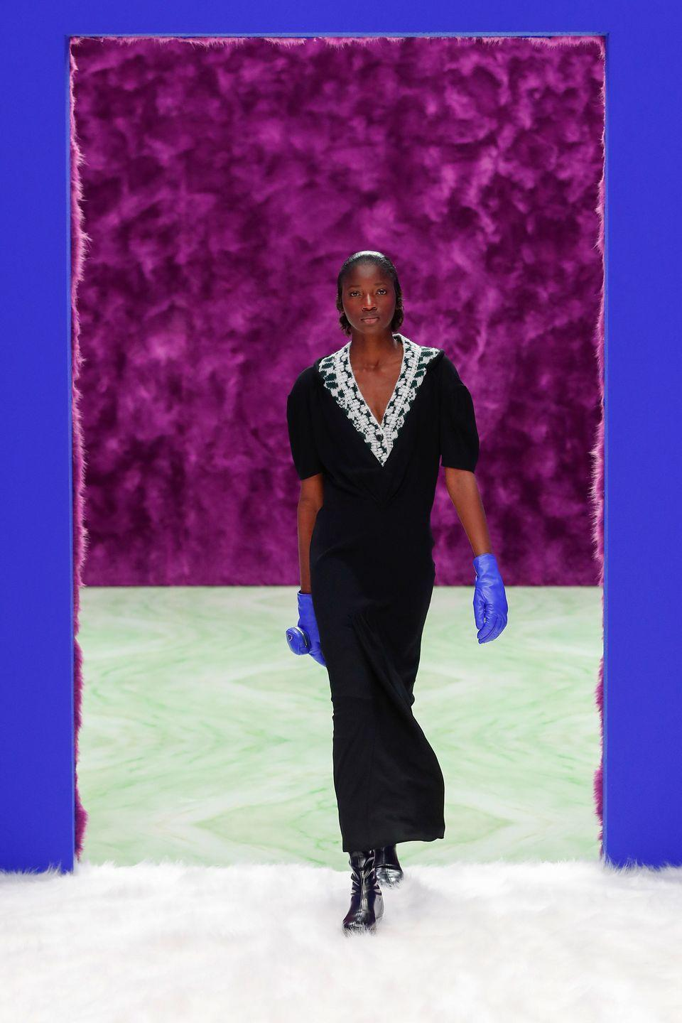 """<p>The latest installment from the partnership made in fashion dreams—Miuccia Prada and Raf Simons—is inspired by change, transformation, and opening possibilities. Those ideas live in jacquard knits, statement faux furs, menswear inspired suiting, bold colored coats, and feminine skirt suits. The looks are only seemingly simple—with bold hits of color like cobalt and orange, against black, brown, and white. Models walked on an interior landscape created out of vibrant faux fur and marble by Rem Koolhaas and AMO. All of it will be eventually donated to Meta, a circular economy project based in Milan, """"which offers<br>sustainable solutions to waste disposal within ephemeral events by collecting and recovering materials for selling and rentals."""" This is the future—clothes to collect and not discard, an awareness around waste, a venture into creativity with thought for what happens next.<em><br>-Kerry Pieri</em></p>"""