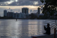 A man takes pictures with his cellphone on the banks of the Condado lagoon, where multiple selective blackouts have been recorded in the past days, in San Juan, Puerto Rico, Thursday, Sept. 30, 2021. Power outages across the island have surged in recent weeks, with some lasting up to several days. (AP Photo/Carlos Giusti)