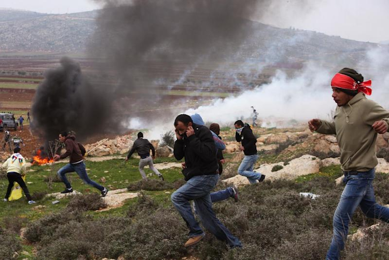 Palestinian protesters take cover from tear gas thrown by Israeli security forces during clashes following a demonstration against Israeli settlements in the West Bank village of Turmus Aya, north of Ramallah on December 19, 2014